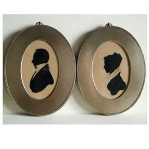 Pair of painted silhouettes in brass frames 1820